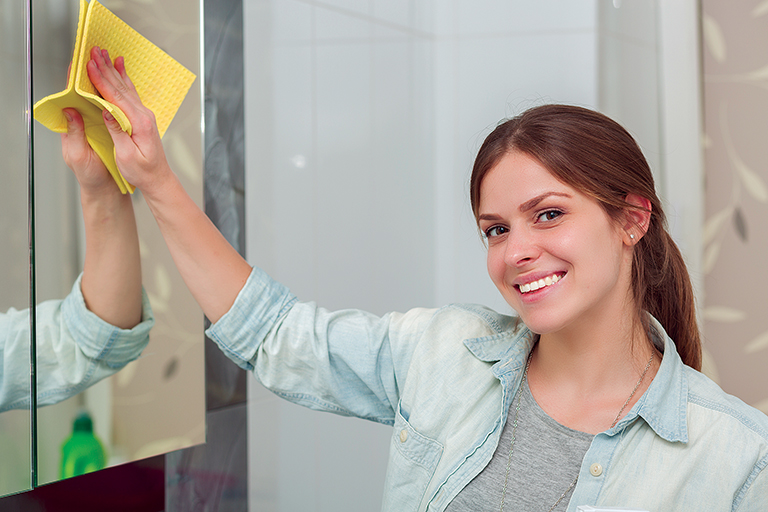 Woman Cleaning Mirror